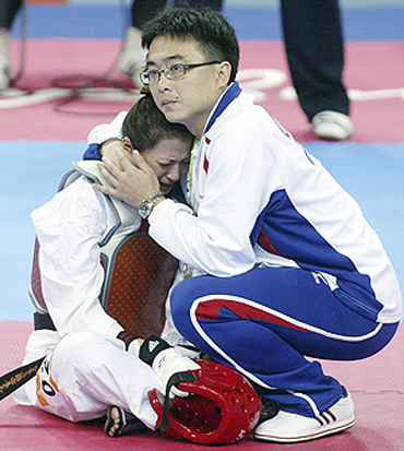 Taiwan's Yang Shu-Chun is consoled by her coach while staging a sit-in protest