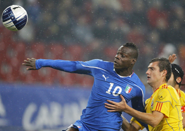Italy's Mario Balotelli (L) and Romania's Gabriel Tamas fight for the ball during their friendly soccer match in Klagenfurt