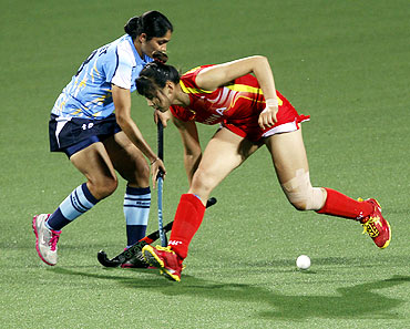 India's Jasjeet Kaur Handa (L) defends against China's Song Qingling during their field hockey game at the 16th Asian Games in Guangzhou