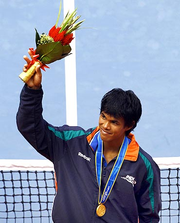 India's Somdev Devvarman celebrates with his gold medal after his men's tennis final win over Uzbekistan's Denis Istomin at the 16th Asian Games in Guangzhou