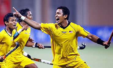 Malaysia's Muhamad Amin Rahim celebrates after scoring the winning goal against India in their men's semi-final field hockey game at the 16th Asian Games in Guangzhou