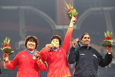 China's gold medalist Li Yanfeng (C) stands with compatriot silver medalist Song Aimin and India's bronze medalist Krishna Poonia after the women's discus throw final during the 16th Asian Games in Guangzhou