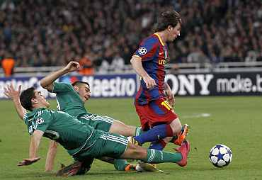 Barcelona's Lionel Messi is challenged by Panathinaikos' defenders during their match in Athens