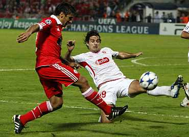 Hapoel Tel Aviv's Shechter fights for the ball with Benfica's Salvio during their match in Tel Aviv