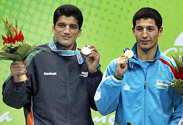 Elshod Rasulov (R) of Uzbekistan stands with Dinesh Kumar of India after their men's 81kg gold medal boxing match at the 16th Asian Games in Guangzhou