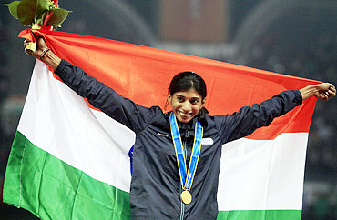 India's Ashwini Chidananda Akkunji celebrates with her gold medal after winning the women's 400m hurdles event at the 16th Asian Games in Guangzhou