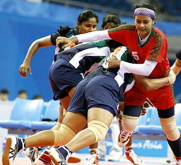 The Indian players tackle a Bangladesh player during the women's kabaddi group match game at the Asian Games