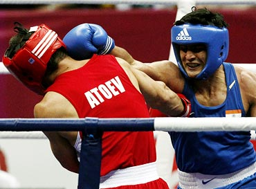 Vijender Singh (right) lands a punch on Abbos Atoev of Uzbekistan