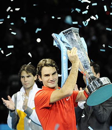 Roger Federer lifts the trophy as Rafael Nadal applauds after their World Tour Finals match on Sunday