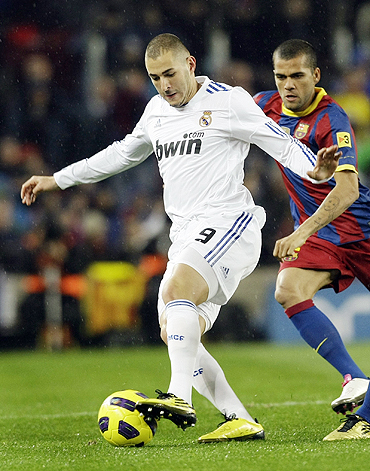Real Madrid's Karim Benzema (left) and Barcelona's Dani Alves vie for possession