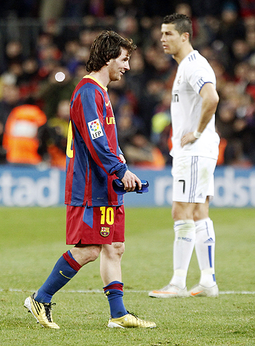 Barcelona's Lionel Messi (left) walks past Real Madrid's Cristiano Ronaldo