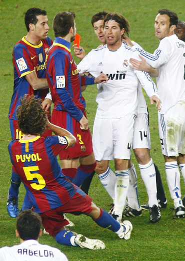 Barcelona's Carles Puyol (bottom left) is pushed to the ground by Real Madrid's Sergio Ramos (2nd from right) during their match at Nou Camp on Monday