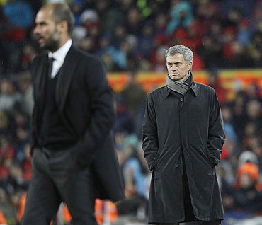 Jose Mourinho (right) and Pep Guardiola react during the 'El Clasico' on Monday
