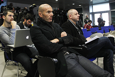 Real Madrid's first team adviser Zinedine Zidane listens to Jose Mourinho at a news conference