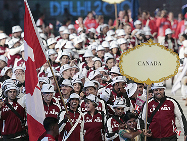 Flag bearer Ken Pereira of Canada leads his delegation into the Jawaharlal Nehru Stadium during the opening ceremony