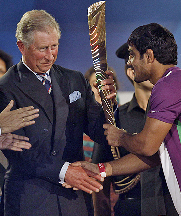 Britain's Prince Charles (left) receives the Queen's Baton from Indian wrestler Sushil Kumar during the opening ceremony