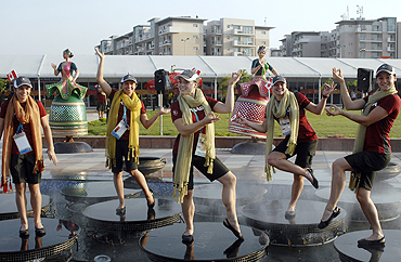 Members from the Canadian team pose at a water fountain at the Game Village