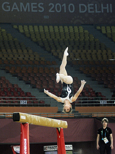 A gymnast practises on the balance beam during a training session inside the Indira Gandhi Sports Complex in New Delhi
