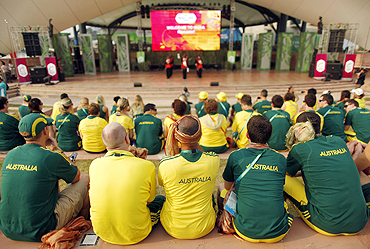 Australian team members watch the team's flag-raising ceremony at the Commonwealth Games Village in Delhi
