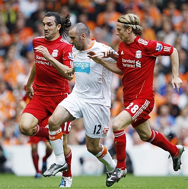 Liverpool's Kyrgiakos and Poulsen chase Blackpool's Taylor-Fletcher during their English Premier League