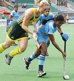 India's Subhadra Pradhan (right) goes past Australia's Megan Rivers during their hockey group match on Wednesday