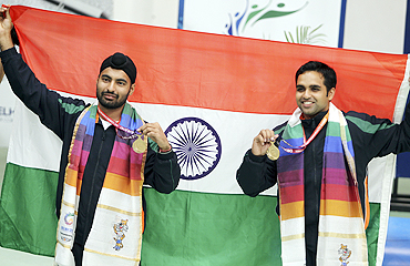 Indian gold medallists Gurpreet Singh (left) and Omkar Singh with the national flag after winning the men's pairs 10m air pistol shooting final on Thursday