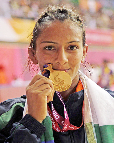 Gold medallist Geeta poses after winning the 55kg women's freestyle wrestling match on Thursday