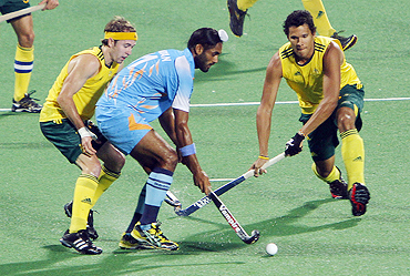India's Saravanjit Singh (centre) is challenged by Australia's Joel Carroll (right) and Matthew Swann during their hockey group match on Thursday