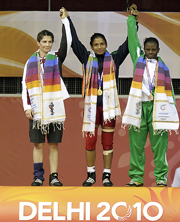Gold medallist Alka Tomar of India (centre), silver medallist Tonya Verbeek (left) of Canada and bronze medallist Tega Tosin Richard of Nigeria pose on the podium after their 59kg women's freestyle wrestling event on Friday