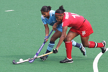 Trinidad and Tobago captain Patricia Wright-Alexis (right) and India's Poonam Rani fight for the ball during their women's hockey group match on Friday