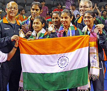 Indian table tennis stars Mouma Das, Shamini Kumaresan, Poulomi Ghatak, Mamta Prabhu and Madhurika Suhas with their coaches Marcos Constantini (right) and Bhawani Mukherjee (left) after winning the silver medal on Saturday