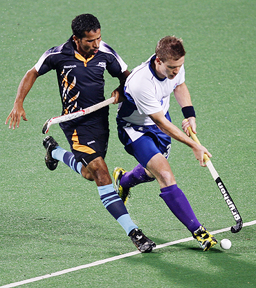Scotland's Derek Salmond (right) and India's Bharat Chiraka fight for possession during their men's hockey group match on Saturday