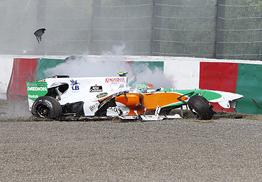 Force India's Liuzzi car rams into the wall after colliding with Ferrari's Massa