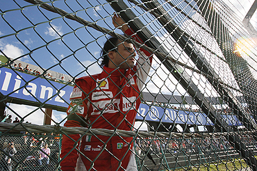 Ferrari's Felipe Massa looks out from behind a fence as his car is recovered after colliding with Force India's Vitantonio Liuzzi