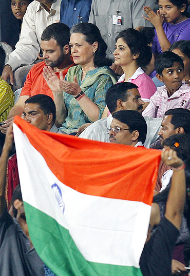 Congress party president Sonia Gandhi and her son Rahul Gandhi (top left) applaud after India's win over Pakistan at the men's hockey group match on Sunday