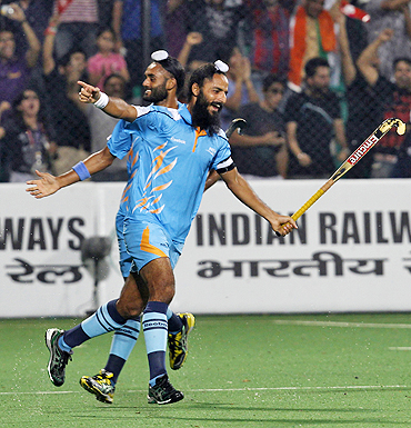 India's hockey players Sarvanjeet Singh (left) and captain Raj Pal Singh celebrate after scoring against Pakistan on Sunday