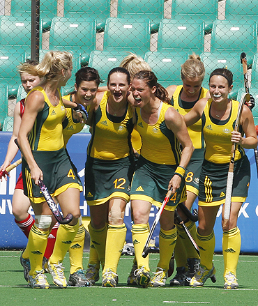 Australian players celebrate after scoring against England in their women's hockey semi-final tie on Monday