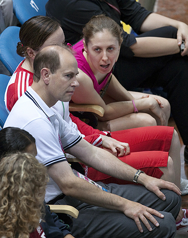 Australian diver Briony Cole chats with Britain's Prince Edward (left) during the men's three metre springboard diving at the Commonwealth Games in New Delhi on Monday