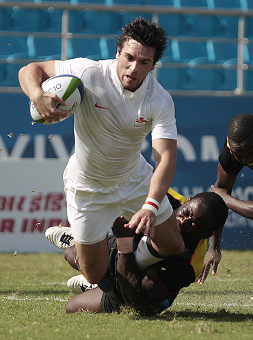 Uganda's Robert Sseguya fails to prevent England's Mathew Turner from scoring during their rugby sevens pool match on Monday