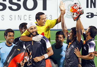 Indian hockey players celebrate after securing a place in the final by beating England in a penalty shootout on Tuesday
