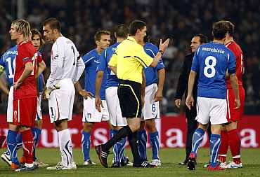 Referee Thomson gestures after suspending the Euro 2012 qualifying match between Italy and Serbia