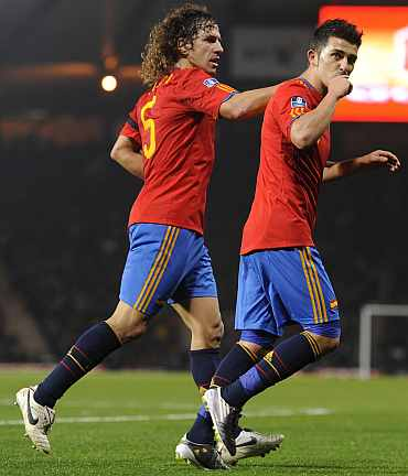 David Villa celebrates with Puyol after scoring