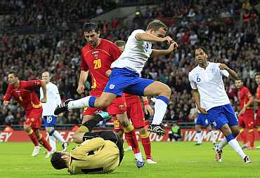 England's Kevin Davies jumps over Montenegro's goalkeeper Mladen Bozovic during their Euro 2012 qualifying match