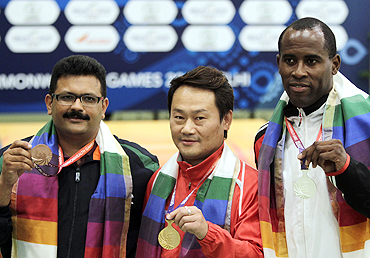 Singapore's gold medallist Gai Bin (centre) poses with Trinidad's silver medallist Peter Roger Daniel (right) and India's bronze medallist Samaresh Jung after winning the men's singles 25m standard pistol shooting finals on Wednesday
