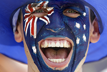 A New Zealand hockey fan cheers for his team during their bronze medal match against England