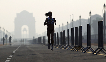 Michelle Cope of England runs past India Gate while competing in the women's marathon final on Thursday