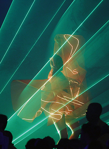 A dancer, illuminated by lasers, performs during the Commonwealth Games closing ceremony
