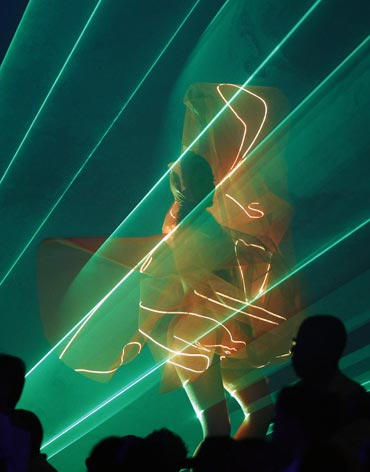 A dancer, illuminated by lasers, performs at the Jawaharlal Nehru stadium