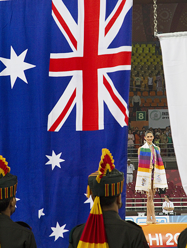 Australia's Naazmi Johnson watches her national flag is raised after winning gold during rhythmic gymnastics event on Wednesday