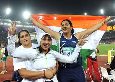 India's Krishna Poonia, Harwant Kaur and Seema Antil celebrate after winning medals